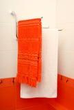Två handdukar är i ett orange badrum Arkivfoton