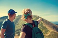 Två handelsresande diskuterar om resplan på överkanten av berghil Royaltyfri Foto