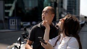 Två handelsresande i en storstad känner igen de ställen, som ses i smartphonen, och tar foto arkivfilmer