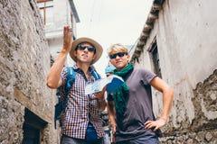 Två handelsresande som är borttappade i ändlös asiatisk gatalabyrint arkivbilder