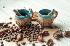 Två handgjorda koppar kaffe för liten gammal krukmakeri, kaffebönor, torkade data för sötsak och kanelbruna pinnar Royaltyfri Fotografi