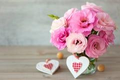 Två handgjorda valentin hjärtor och härliga blommor Arkivfoton