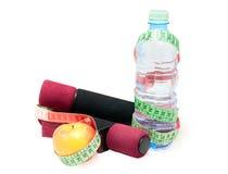 Två hantlar, äpple, måttband, flaska med vatten på en vit royaltyfri bild