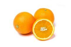 Två hela apelsiner och halvt Arkivbild