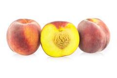 Två hela persika och halvan persika Arkivfoton