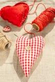 Två hemlagade sydde röda bomullsförälskelsehjärtor Arkivfoto