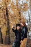 två hemtrevliga unga flickor går på hösten parkerar den vägen för att göra foto arkivfoto