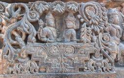 Två hinduiska gudar i sniden kunglig vagn Lord Shiva och hans fru Parvati på den skulpterade väggen av den 12th centurtemplet, In Arkivfoton