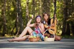 Två hippieflickor med gitarren i en sommarskog Arkivfoto