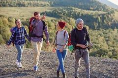 Två hipsterpar med ryggsäckar som fotvandrar i bergen under lång tur Den lyckliga caucasian gruppen av handelsresande har royaltyfri fotografi