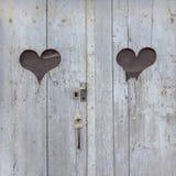 Två hjärtaformer på antik trädörr fotografering för bildbyråer