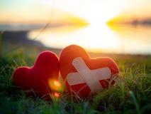 Två hjärtor bredvid sjön på sensethimmelbakgrund Par förälskelse, Valentine Concept arkivfoto