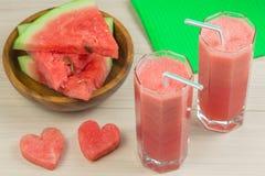 Två hjärtor, glass exponeringsglas för vattenmelonfruktsaft itu med ett sugrör på en ljus träbakgrund, en läcker coctail, a Royaltyfri Bild
