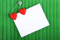 Två hjärtor med ett kort till ett meddelande Arkivbilder