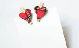 Två hjärtor med materialet, med träomfamningar som klämmas fast till kortet Arkivfoto