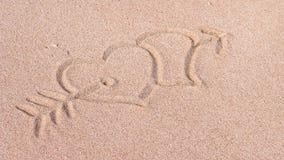 Två hjärtor och pil, oss hjärta det som dras på sand på stranden, Bali, Indonesien Royaltyfri Fotografi