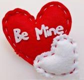 Två hjärtor på en vit bakgrund med ` är min ` som är skriftlig på den större Arkivbild