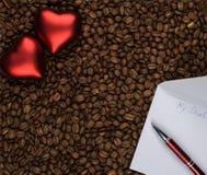 Två hjärtor på kaffe med förälskelsebokstaven royaltyfri foto