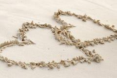Två hjärtor som är skriftliga i sand på en strand Arkivbilder