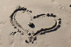 Två hjärtor som en på en strand arkivfoto
