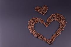 Två hjärtor som fodras från kaffe, lokaliseras till rätten av mitten av bakgrunden royaltyfria bilder