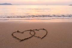 Två hjärtor som tecknas i strand Royaltyfri Foto
