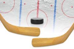 Två hockeypinnar, puck och hockeyfält Arkivbilder