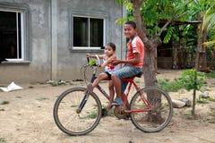 Två honduranska barn som sitter på cykeln i lantlig by Arkivbild