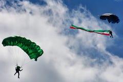 Två hoppa fallskärm landning från en molnig himmel Arkivbild