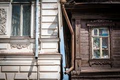 Två hus i Ryssland: gammalt trä och tegelsten. Arkivbilder