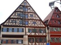 Två hus med olika färger och massor av fönster med några reflexioner på fönstren i staden av Dinkelbur i Tyskland royaltyfri bild