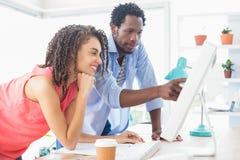 Två idérika affärskollegor som håller ögonen på datoren arkivfoto