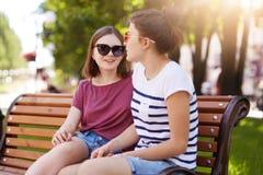 Två idérika flickor talar och skrattar, medan sitta på bänk utomhus Unga och funloving vänner delar det nya idéer, tankar och pla royaltyfri foto