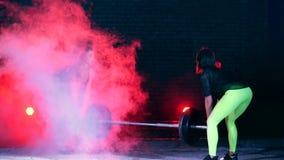 Två idrotts- flickor i par som gör olik styrka, övar med en skivstång, på natten, i ljus av mångfärgat stock video
