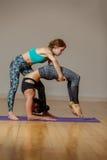 Två idrotts- kvinnor som utför yoga arkivfoto