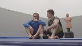 Två idrotts- män som sitter på golvet i idrottshallen som vilar, når utbildning Par av svarta boxas handskar och vattenflaskan lager videofilmer