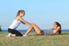 Två idrottskvinnor som gör knastranden arkivfoton