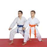Två idrottsman nen med det orange bältet och blåttbältet står i kugge Fotografering för Bildbyråer