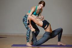 Två idrottsman nen som gör yogaövningar arkivfoto