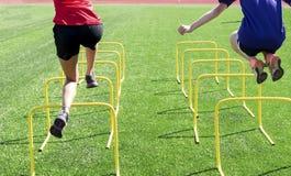 Två idrottsman nen som hoppar över gula mini- häckar arkivfoton