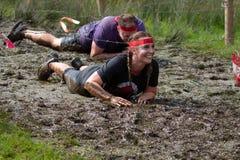 Två idrottsman nen som kryper till och med gyttja i ett 10km hinderlopp royaltyfri foto