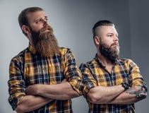 Två iklädda brutala skäggiga män en plädskjorta royaltyfri foto