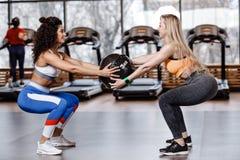 Två iklädda idrotts- flickor en sportswear gör tillsammans tillbaka squats med den tunga konditionbollen i den moderna idrottshal royaltyfria foton