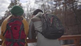 Två iklädda omslag och hattar för turister som står på bron nära flodsamtalet och att tycka om naturen Semester av a arkivfilmer