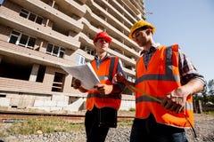 Två iklädda skjortor för väg-och vattenbyggnadsingenjör, orange arbetsvästar och hjälmar går nära mång--våningen byggnaden arkivfoto