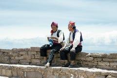 Två iklädda traditionella dräkter för män som är specifika för den Taquile öregionen, en av dem som sticker en hatt Arkivfoton