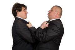 Två ilskna affärskollegor under ett argument som isoleras på vit bakgrund arkivfoto