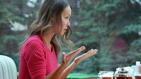 Två ilskna kvinnor som talar över en kopp te Arkivfoton