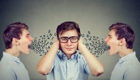 Två ilskna män som skriker på den fridsamma grabben som täcker hans öron med händer som ignorerar dem Arkivbild