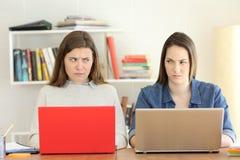 Två ilskna studenter som ser sig med hat royaltyfri fotografi